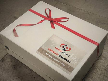 Goodie Box Karton in weiß mit roter Schleife für die virtuelle Weihnachtsfeier von der VirtuaLounge