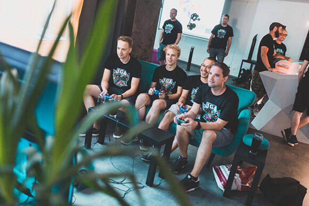 4 Männer eines Junggesellenabschieds sitzen an den Konsolen im Eingangsbereich und zocken in der VirtuaLounge