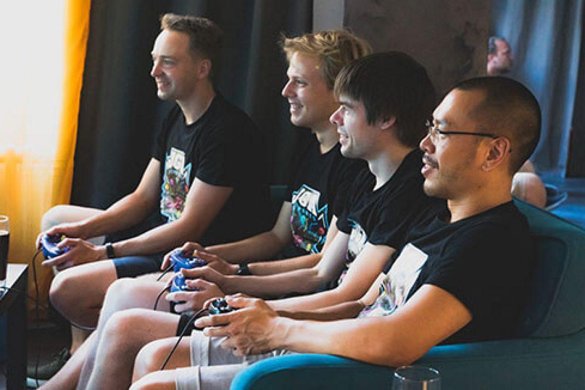 4 Männer sitzen an den Konsolen im Eingangsbereich und zocken in der VirtuaLounge