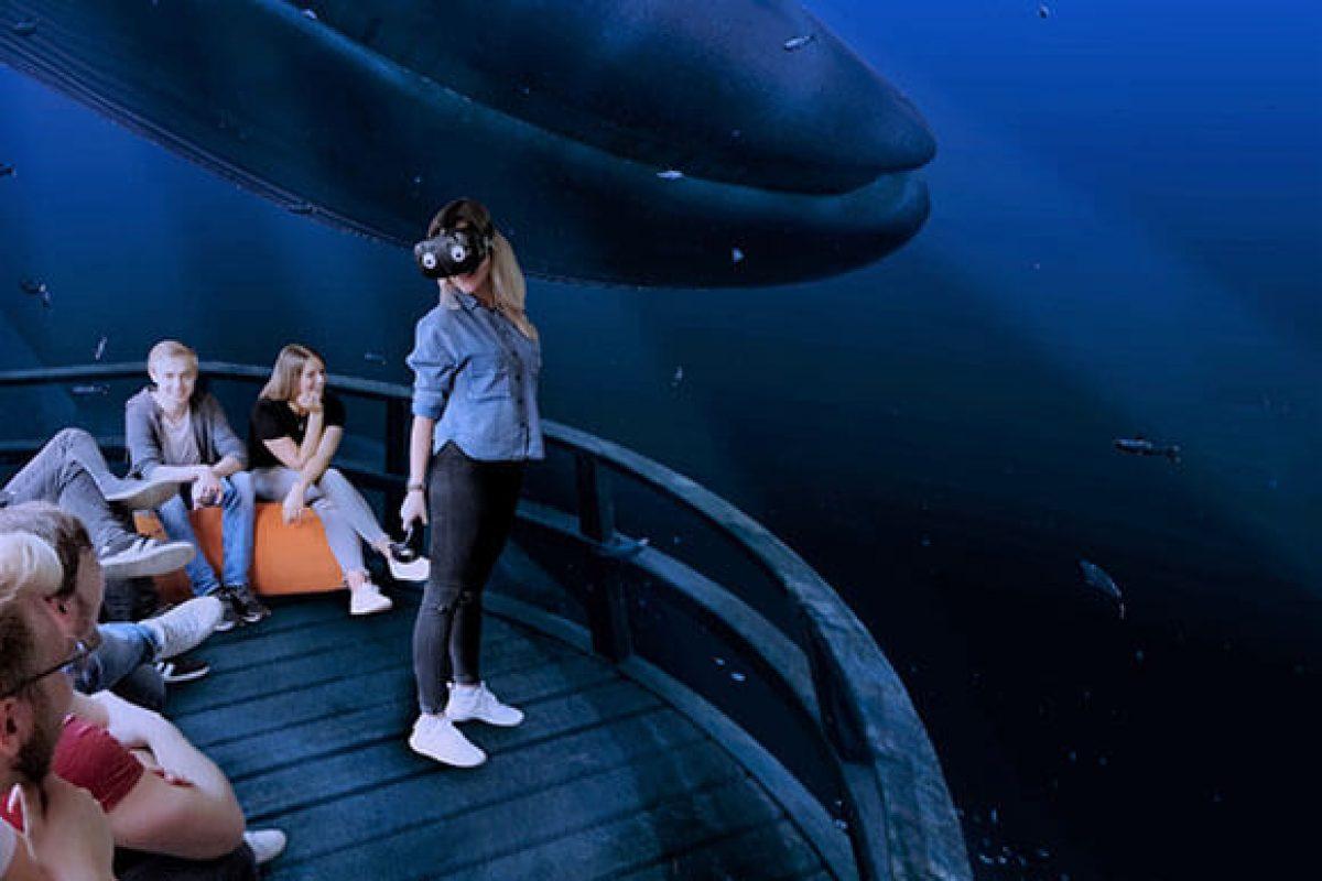 Eine Frau erlebt in Virtual Reality eine Unterwasserwelt in der VirtuaLounge